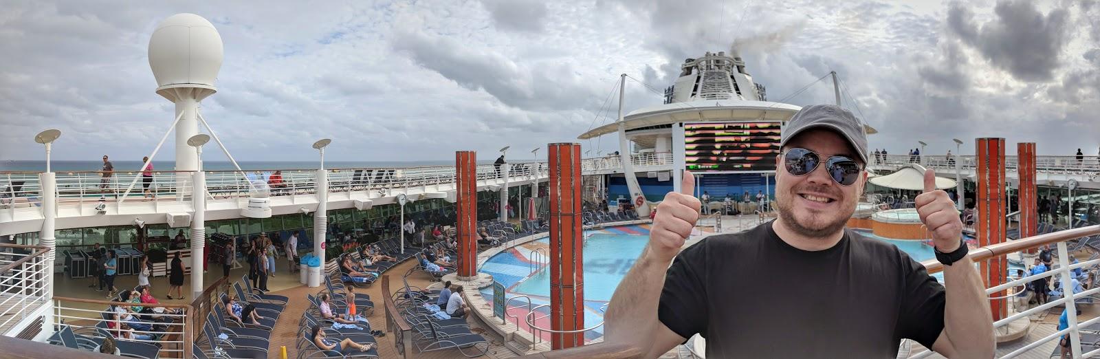 Panorama av øverste dekk, med bassenger og solsenger. Christoffer smiler og gir tommelen opp.
