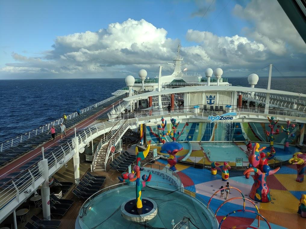 Utsikt mot fronten av båten, med badebassenger og strandstoler langs ripa.